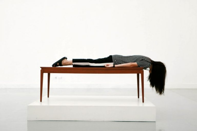 Woman laying face down on a table.