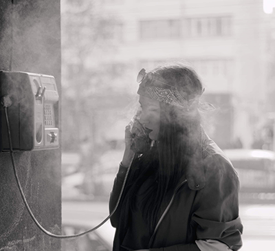 Woman talking on phone in phone booth.